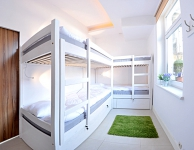 Koedukacyjny pokój wieloosobowy dla 4 osób z umywalką i zamykanymi szafkami dla każdego łóżka. Rozmiar 10 m2. Łazienka wpólna